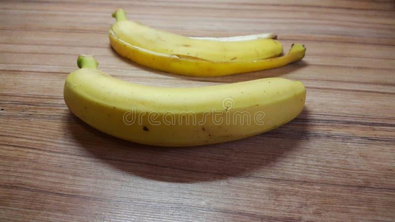 banaan en banaanschil op een houten lijst stock foto's