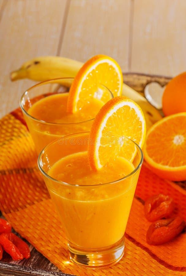 Banaan en sinaasappel smoothie stock afbeeldingen