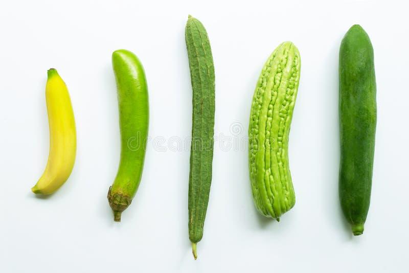 Banaan, groene lange aubergine, luffaacutangula, bittere meloen, groene papaja op wit stock afbeelding