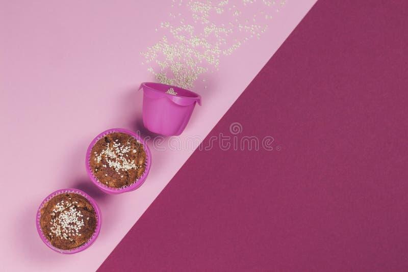 Banaanmuffins met sesam in roze bakselkoppen worden bestrooid op roze en magenta achtergrond die stock foto's