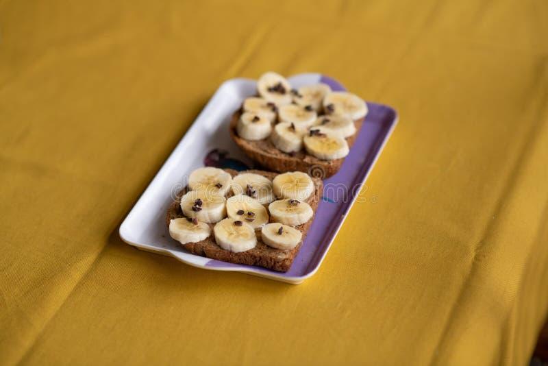 Banaantoost met pindakaas, cacaobonen en honing stock fotografie
