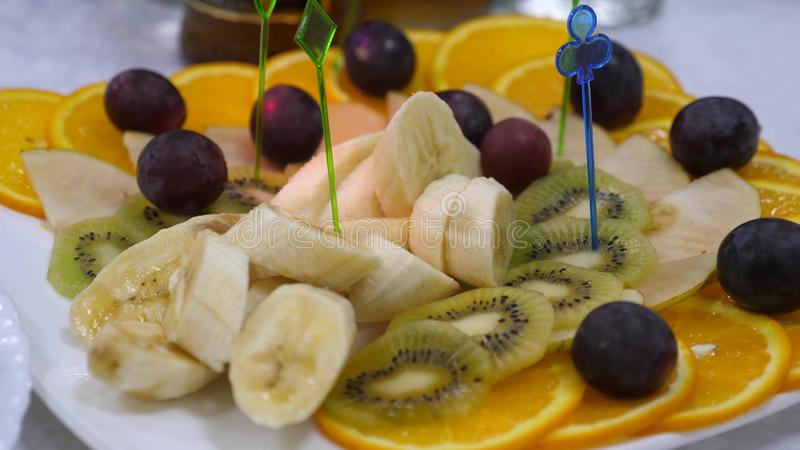 Banai, oranges, grapes, kiwi sliced, close-up. Fresh fruit dish at a festive dining table. Assorted sliced fruit skewers royalty free stock photography