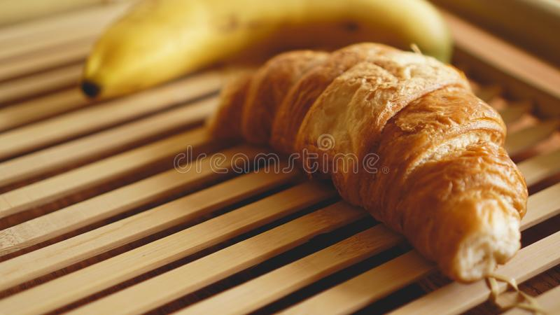 Banan i croissant na nieociosanym drewnianym tle Selekcyjna ostro??, horyzontalna obrazy stock