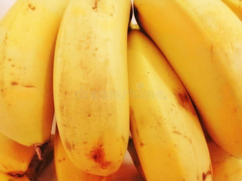 Banan jest ładnym żółtym kolorem z tyłu bielu fotografia royalty free