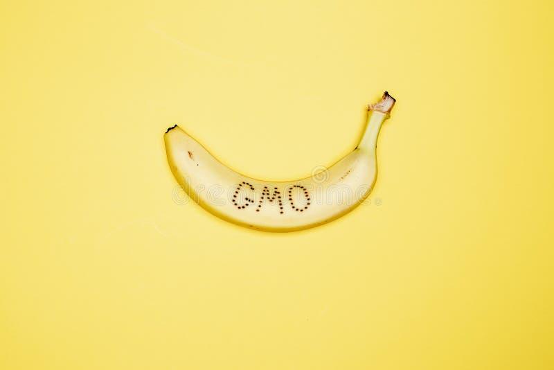 """Banan na łupie z czego słowa """"GMO† piszą kłamstwach na jaskrawym żółtym tle fotografia royalty free"""