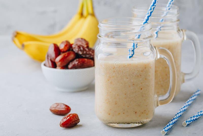 Banan- och datumfruktsmoothie eller milkshake i den glass murarekruset royaltyfria foton
