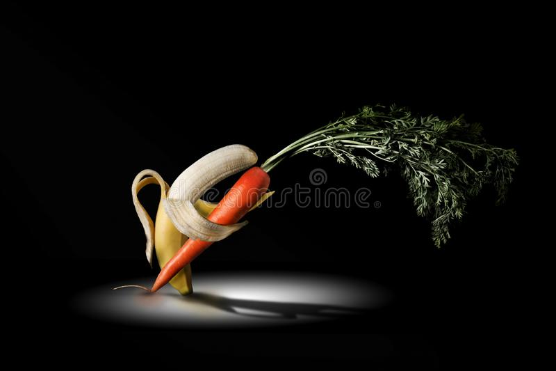 Banan och morot som dacing under en strålkastare royaltyfri bild