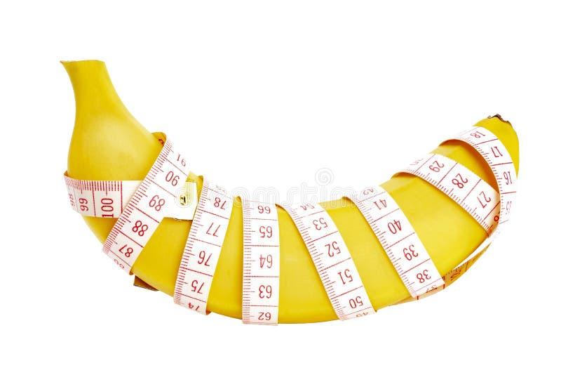 Banan som slås in med att mäta bandet på en vit bakgrund, isolat arkivfoto