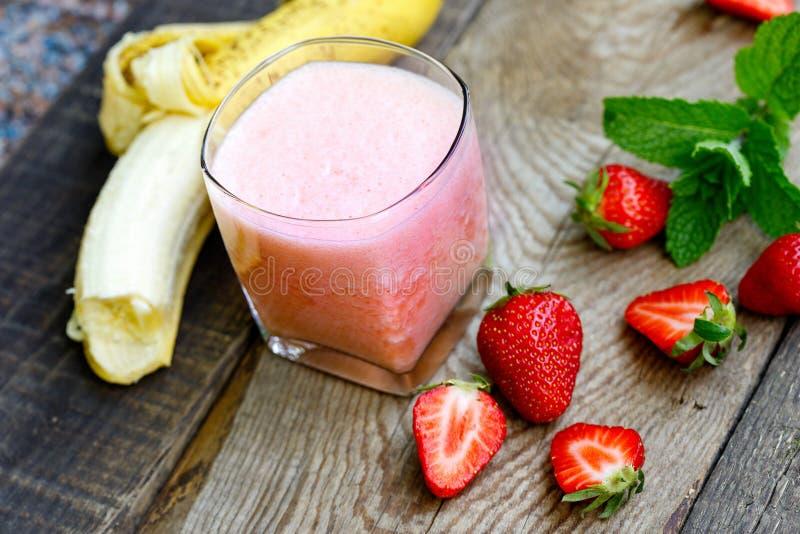 Banan - truskawkowy smoothie w szkle (zdrowy jarski napój) obrazy stock