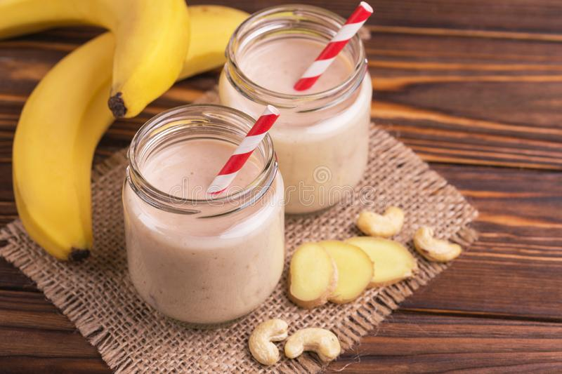 Banana and almond smoothie with ginger in glass jars with paper straws. On rustic wooden table. Horizontal view. Copy space stock photo
