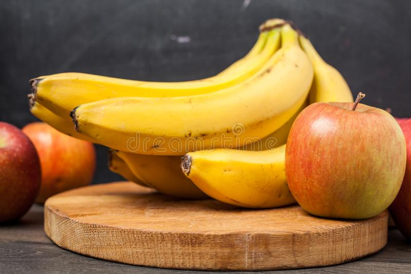 Banana and apple on chopping stock photos