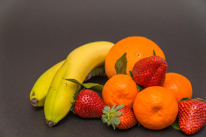banana, apple, orange,strawberries and Three tangerine with leaves on a beautiful gray background, beautiful colors and compositi royalty free stock image