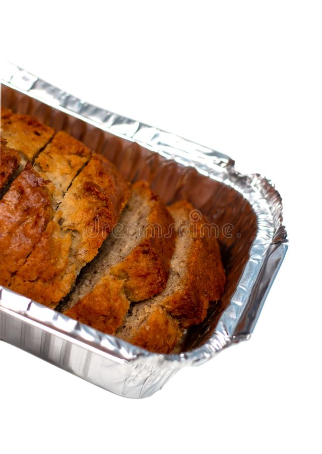 Banana bread loaf cut in pieces isolated on white background. In closeup shot stock photography