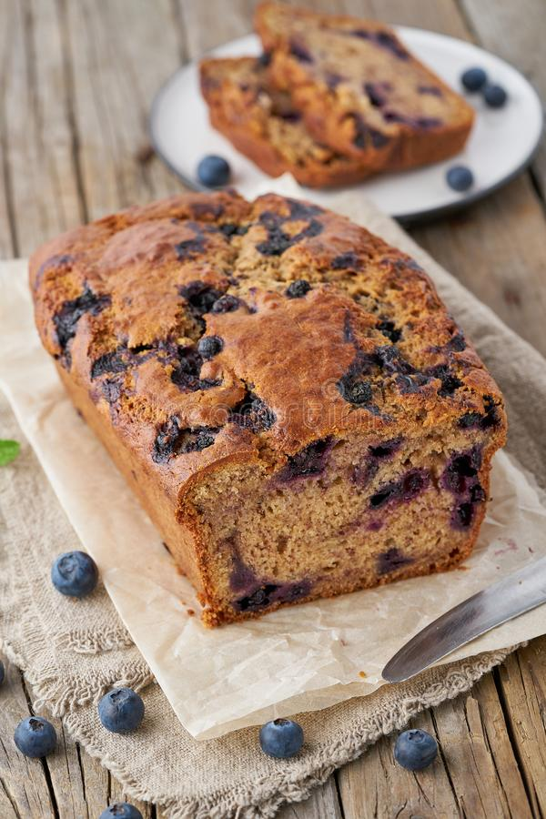 Banana bread on old wooden rustic table, slice of cake with banana, vertical stock photo