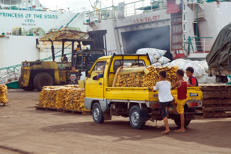 Banana cargo loading in Asian port. Bananas freight on truck waiting on the quay to be loaded into the hold of an old worn ferry amidst the chaotic and unsafe royalty free stock image