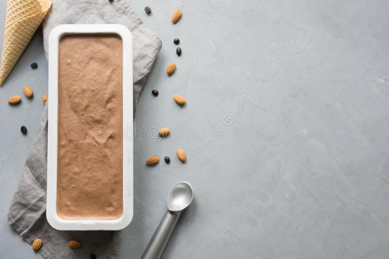 Banana chocolate homemade ice cream in container with coffee beans on grey. Space for text.Top view royalty free stock images