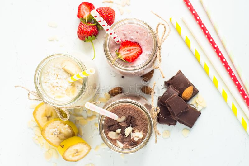Banana chocolate and strawberry milkshakes. Set of milkshake in jars. Banana chocolate and strawberry milkshakes with nuts and coconut. Summer dessert. Top view royalty free stock image