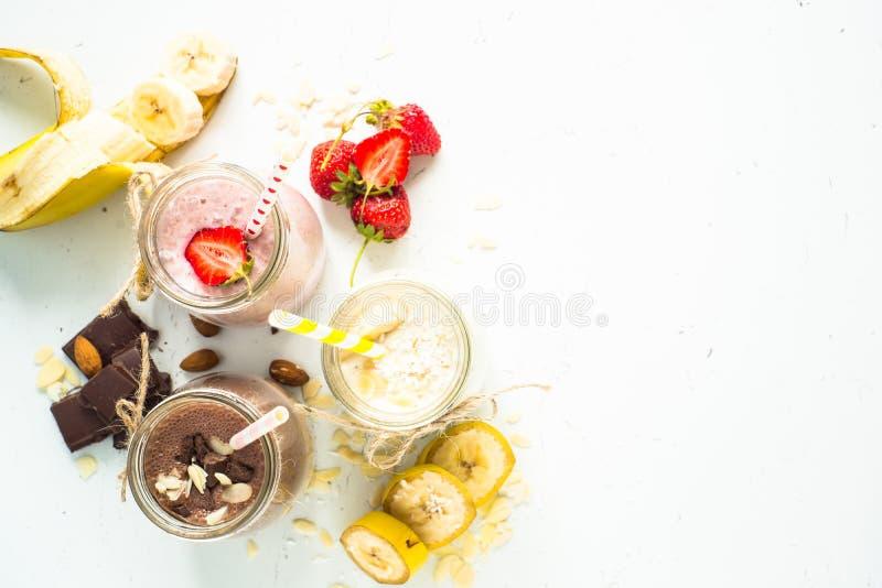Banana chocolate and strawberry milkshakes. Set of milkshake in jars. Banana chocolate and strawberry milkshakes with nuts and coconut. Summer dessert. Healthy stock image
