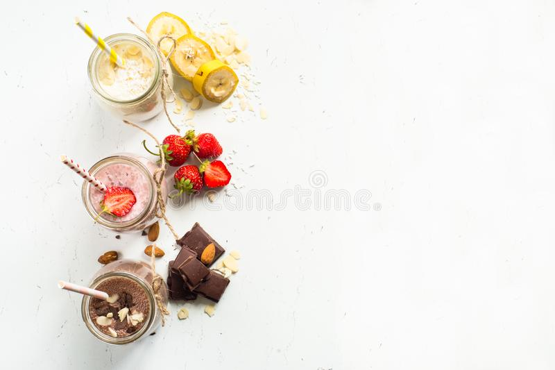 Banana chocolate and strawberry milkshakes. Set of milkshake in jars. Banana chocolate and strawberry milkshakes with nuts and coconut. Summer dessert. Healthy royalty free stock photography
