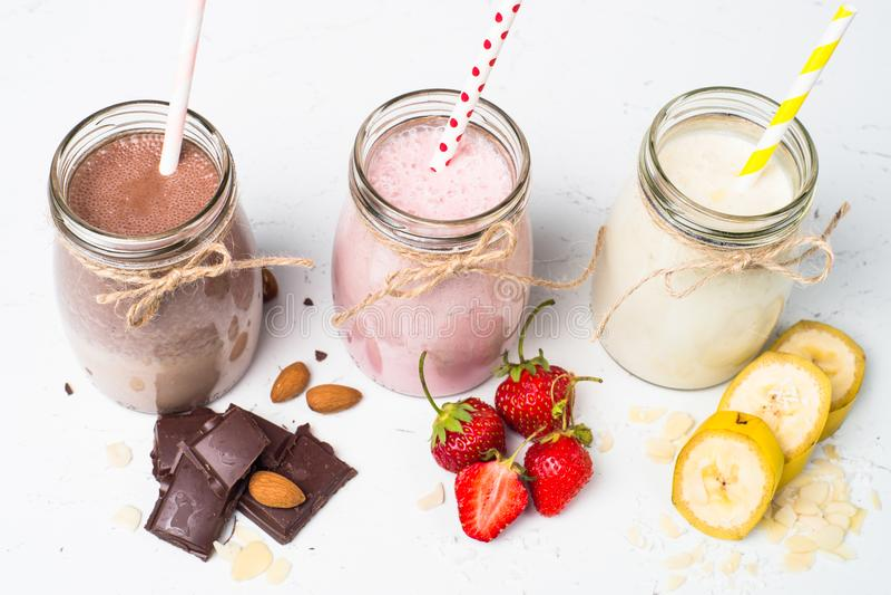 Banana chocolate and strawberry milkshakes. Set of milkshake in jars. Banana chocolate and strawberry milkshakes with nuts and coconut. Summer dessert. Healthy stock photo