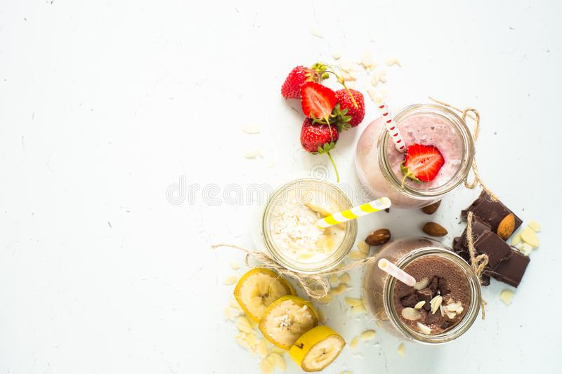 Banana chocolate and strawberry milkshakes. Set of milkshake in jars. Banana chocolate and strawberry milkshakes with nuts and coconut. Summer dessert. Healthy stock images