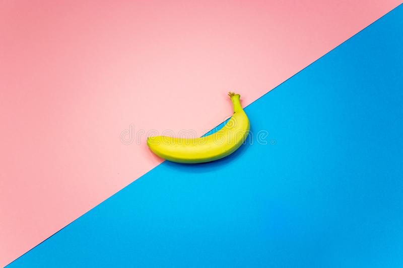 Banana on a colored background. Blue and pink stock image