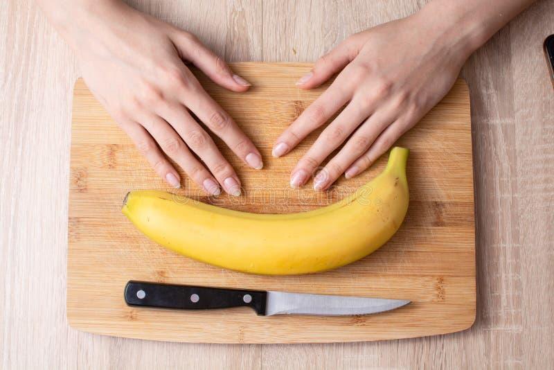 Banana, coltello e mani sulla tavola tagliata di legno immagine stock
