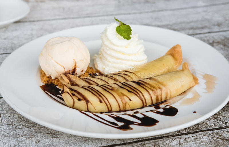 Banana crepes with vanilla ice cream and home made whip creme, glaze with chocolate and honey stock photo