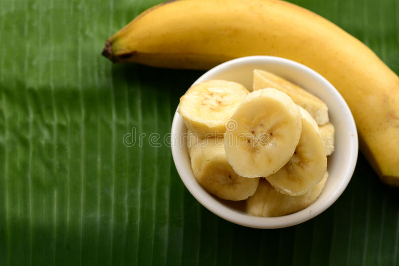 Banana in a cup over a banana leaf stock photo