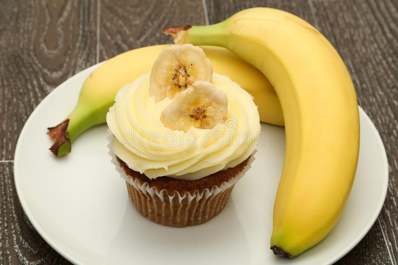 Banana cupcake. A banana cupcake topped with buttercream icing and served with fresh bananas, studio shot royalty free stock photos