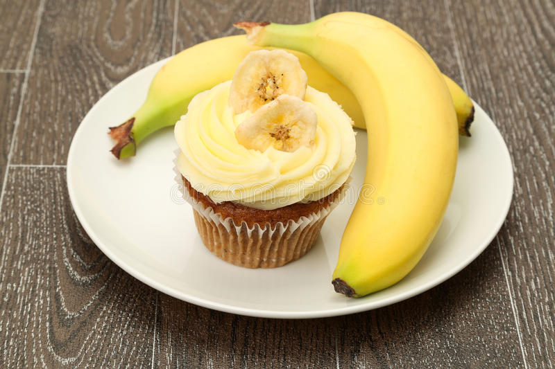 Banana cupcake. A banana cupcake topped with buttercream icing and served with fresh bananas, studio shot royalty free stock image