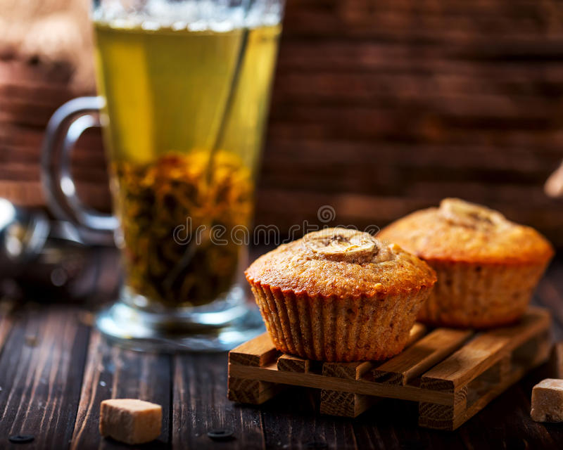 Banana cupcake on a wooden stand. Transparent Cup with green tea. A couple of banana muffins on a wooden stand. Wooden background. Green tea in transparent Cup royalty free stock photos
