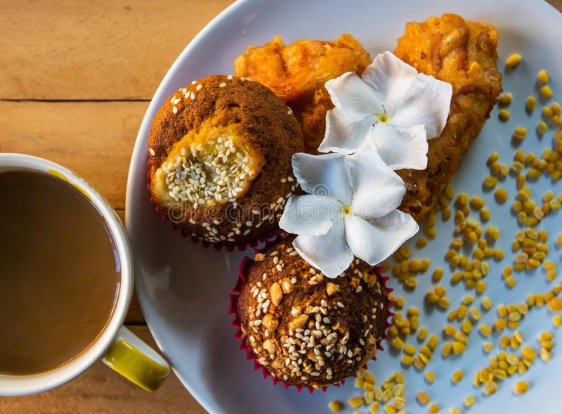 Banana cupcakes with white sesame seeds and peanuts topping with fried chicken served with coffee in the morning, homemade tasty. stock photos