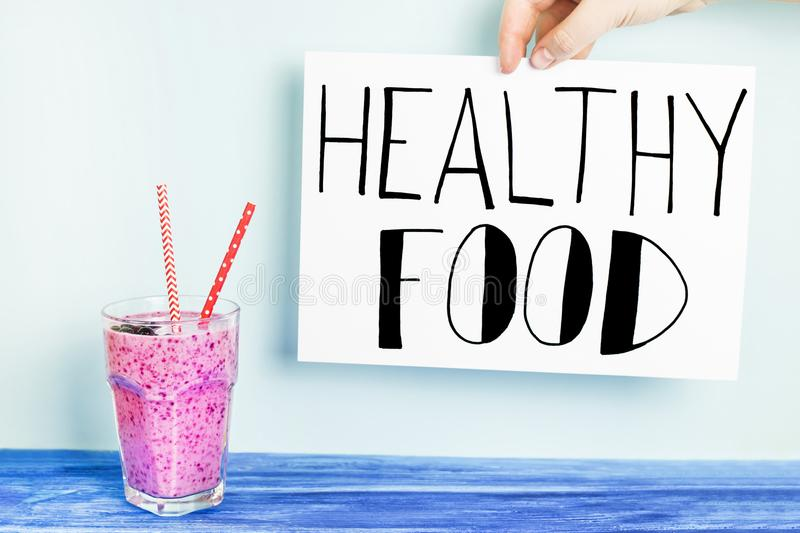 Fruity smoothies on a blue background. Banana currant smoothies of purple color with red straws stand on a wooden table on a blue background with a sign `Healthy stock photography