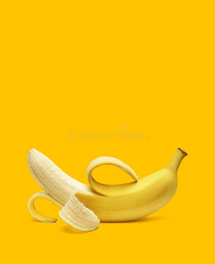 Banana descascada no fundo amarelo imagens de stock