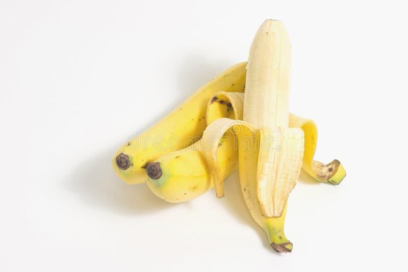 Banana descascada perto de um conjunto de bananas maduras no fundo branco fotografia de stock royalty free