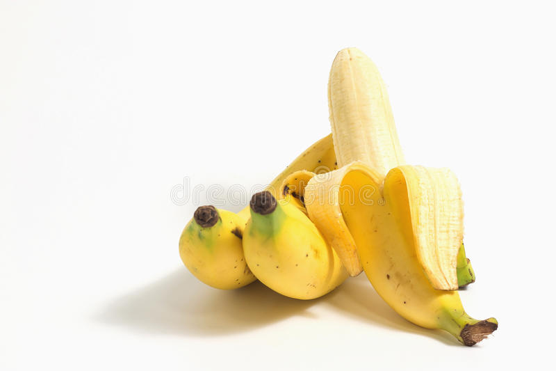 Banana descascada perto de um conjunto de bananas maduras no fundo branco fotos de stock