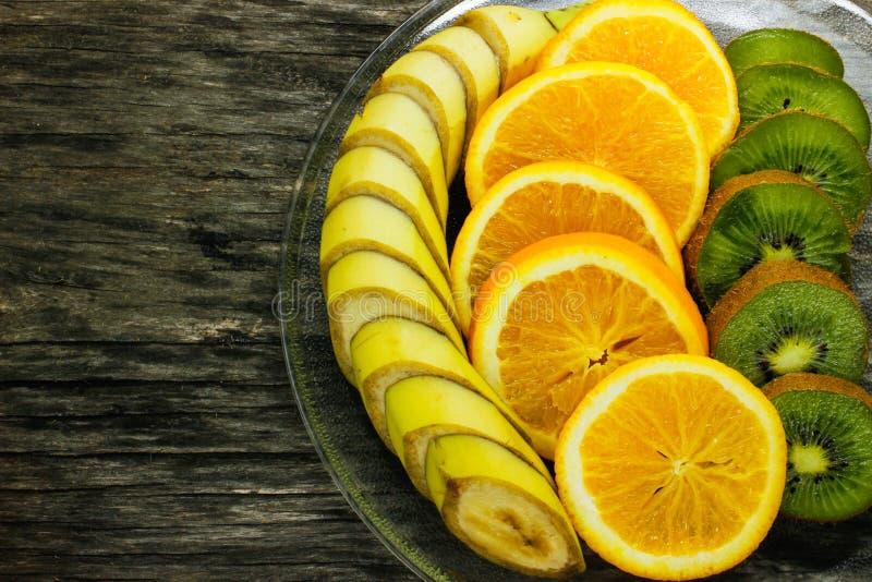 Banana di frutta fresca, kiwi, arancio su fondo di legno Alimento sano Una miscela di frutta fresca Gruppo di agrumi Vegetariano  immagine stock
