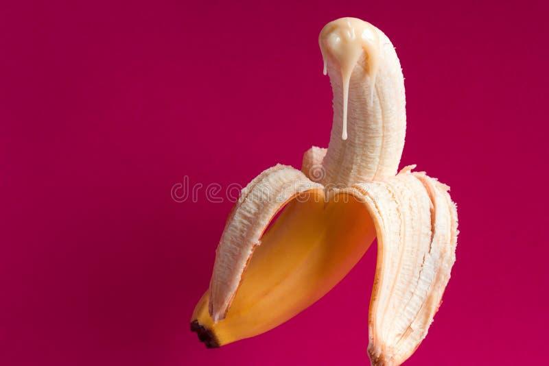 banana e gotas do leite condensado em um fundo cor-de-rosa imagem de stock