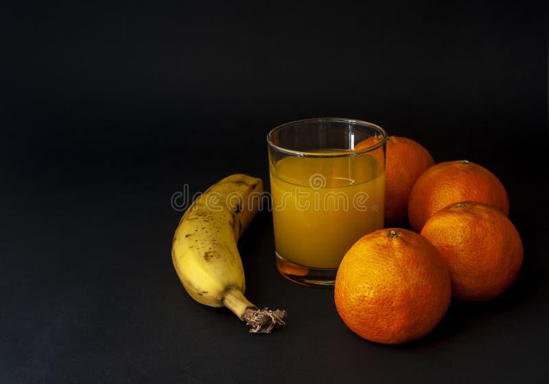 Banana e grupo das tangerinas, os mandarino com vidro do Dr. do suco foto de stock