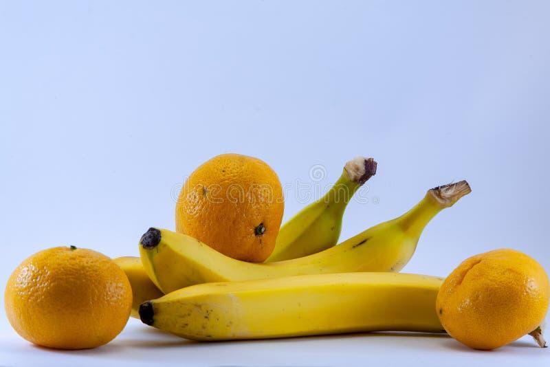 Banana e grupo de tangerinas, os mandarino isolados sobre o branco foto de stock royalty free