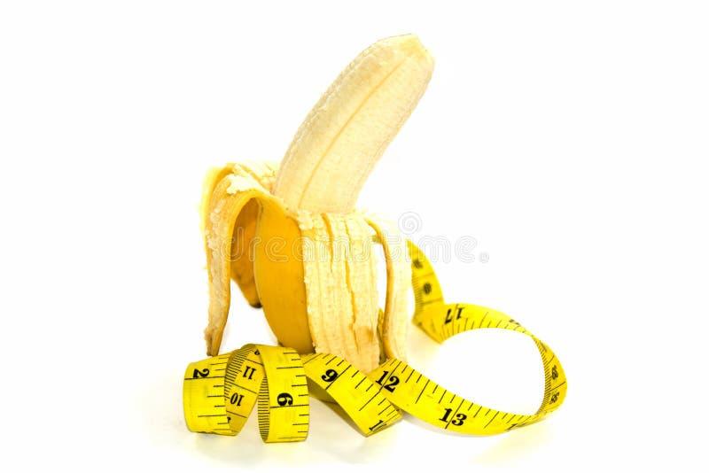 Banana e misura di nastro gialla per il simbolo della dimensione del pene fotografia stock libera da diritti
