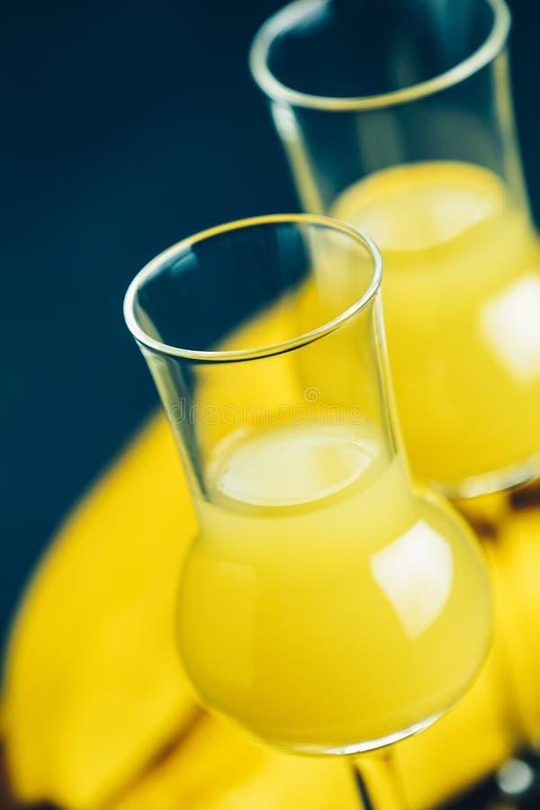 French creme de banana, in  grappas wineglass on dark concrete surface.  European aperitif drink stock photos
