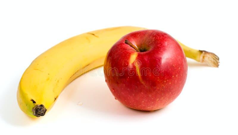 Banana gialla e mela rossa matura fotografia stock