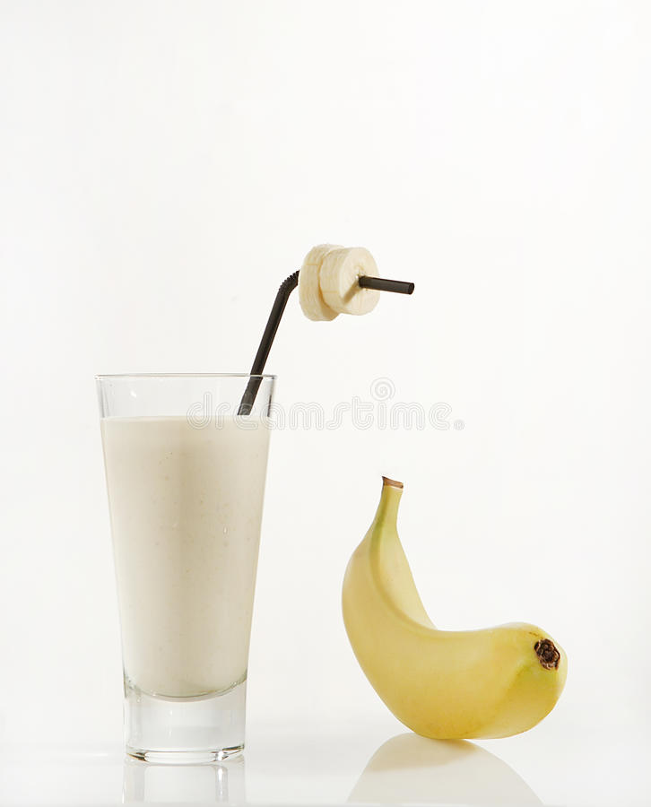Banana and Glass of Milk. A banana next to a glass of milk with a straw and slices of fruit royalty free stock photo