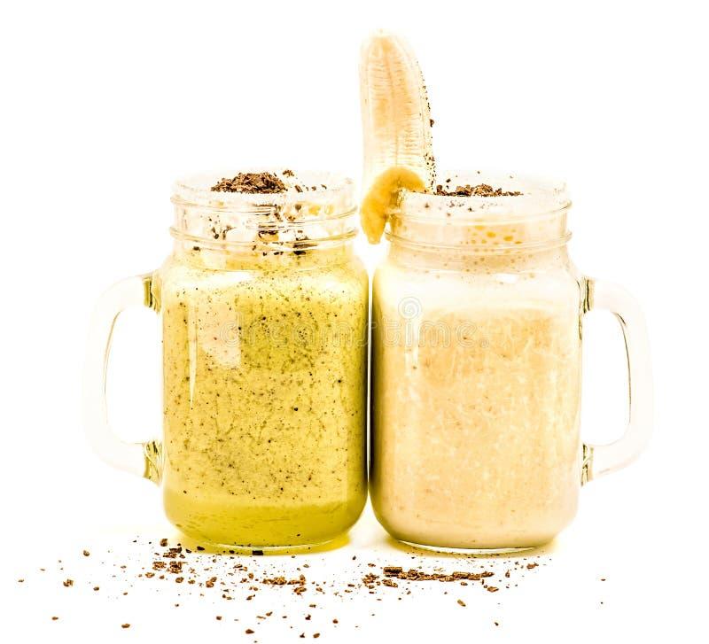 Banana and kiwi milkshakes in mason jars with creme and chocolate on top decorated with banana isolated on white background. Banana and kiwi milkshakes in mason stock images