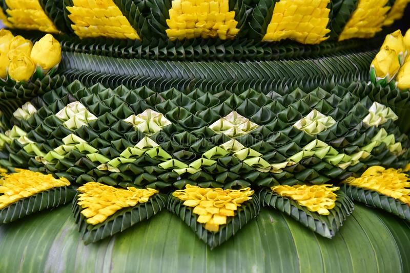 Banana leaf folded into a pattern decorated with many colorful flowers. stock photo