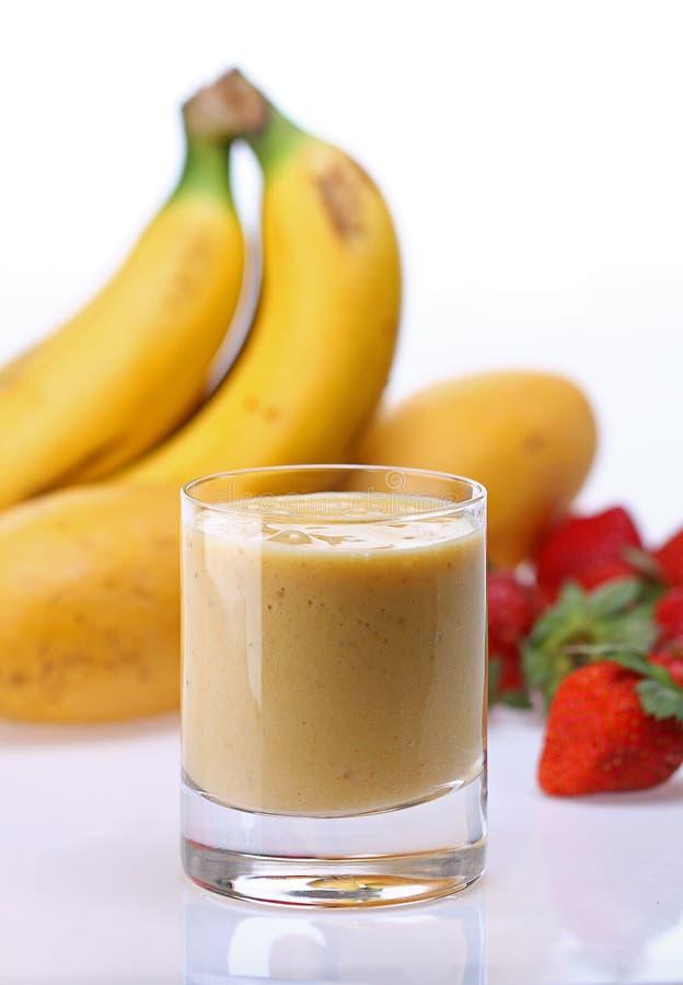 Banana mango strawberry shake. Banana strawberry shake with fruits in background royalty free stock image
