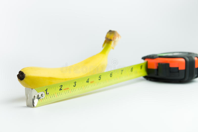 Banana and measuring tape. Close-up of measuring the size of banana on white background royalty free stock images