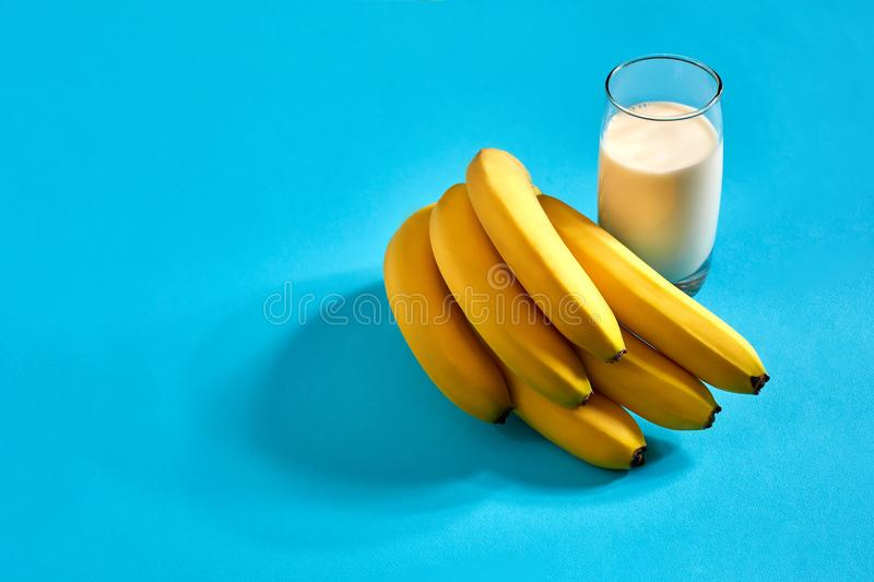 Banana milk drink and a bunch of bananas on a blue background royalty free stock photography